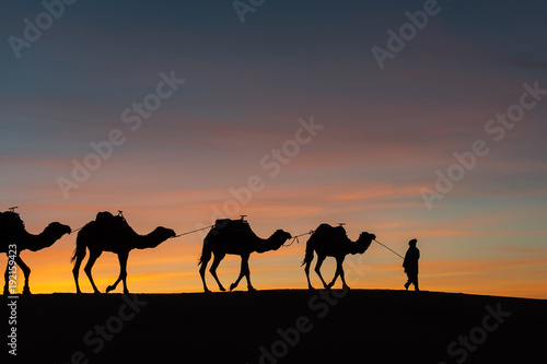 Fotobehang Kameel Silhouette of caravan in desert Sahara, Morocco with beautiful and colorful sunset in background