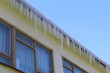 Icicles hanging from the roof of the building.