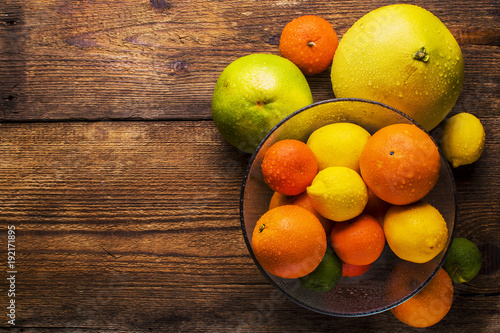 fresh citrus fruits in a glass bowl, top view