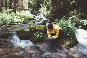Man drink water from clear mountain stream in the lush forest. Wilderness scene
