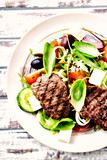 Vegetable salad with grilled steak and olives