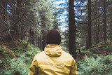 Man in yellow jaket in wild forest. Travel and adventure concept. Mountains landscape photography - 192173426