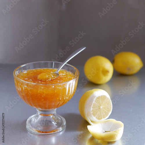 Lemon or orange jam in a transparent glass cup and lemons on a gray background. Spoon with lemon jam.
