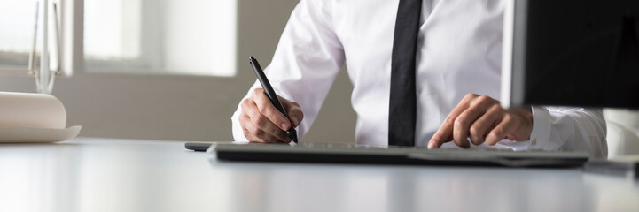 Designer using a tablet and stylus pen in wide panorama low angle view
