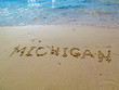 Hand drawn word on sandy beach at Lake Michigan.