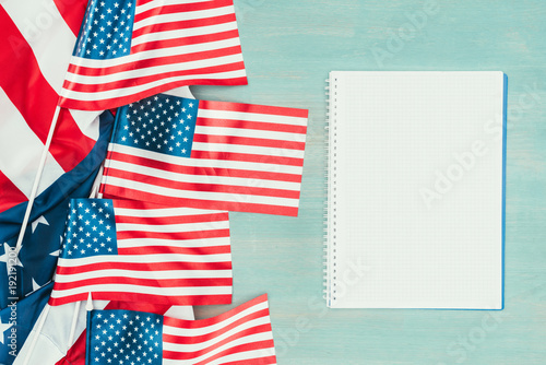 top view of arranged american flags and blank notebook on blue wooden tabletop, presidents day concept