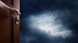 hand opens room door towards a dark sky - 192191621