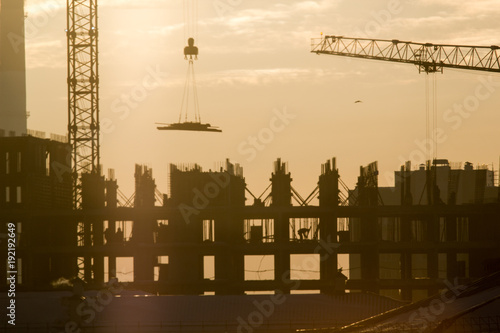 Construction side at sunset - workers, cranes - unfinished building