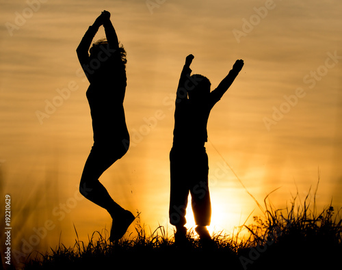 Foto Murales Silhouette of Mom and son in the rays of sunset