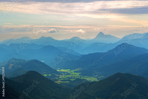 Distant green valley with trees and houses among mountains