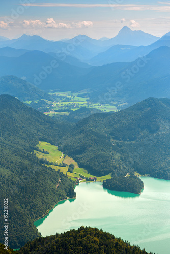 Foto op Aluminium Blauw Walchensee lake and green valley against distant mountains