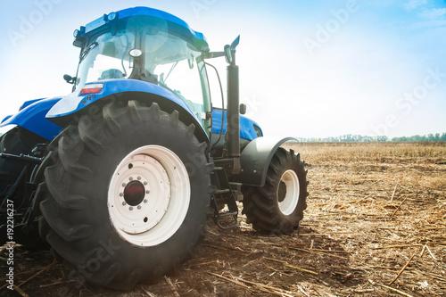 Fotobehang Trekker Blue tractor in a field