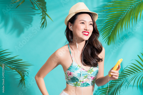 Fotobehang Muziek Fashion pretty asian woman listening music and smiling over bright summer background