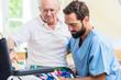 Altenpfleger hilft Senior aus dem Bett in den Rollstuhl - 192223829