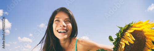 Happy spring flower woman breathing clean air in summer banner background. Asian smiling girl portrait. Outdoor nature happiness.