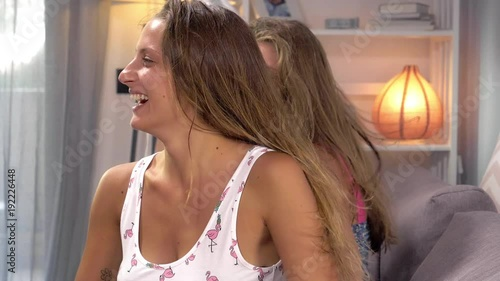Happy girlfriends having fun laughing drying long hair at home slow motion