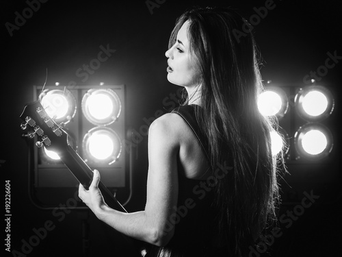 Fotobehang Muziek Young woman playing electric guitar on stage