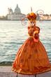 Wonderful orange carnival costume in front of Santa Maria della Salute, Venice