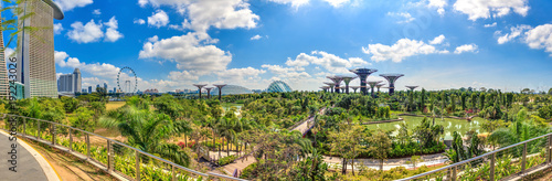 Panoramaaufnahme von erhöhtem Standpunkt über die Gardens by the Bay in Singapur mit Riesenrad und Supertrees fotografiert tagsüber bei blauem Himmel mit lockeren Wolken im März 2015