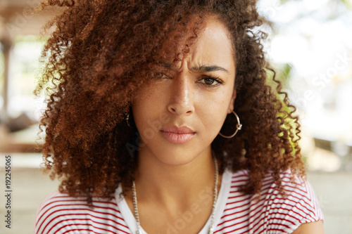 Close up portrait of puzzled discontent female with dark pure healthy skin and frizzy hair, looks in bewilderment at camera, expresses her disagreement and discontent. Embarrassed African woman