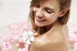 Young pleasant looking female model enjoys hot bath with beutiful flowers, has spa treatments for skin rejuvenation, shows her naked perfect body, cares of appearance. Beauty and care concept