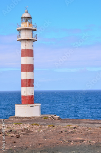 Fotobehang Blauw High Lighthouse near the Coast