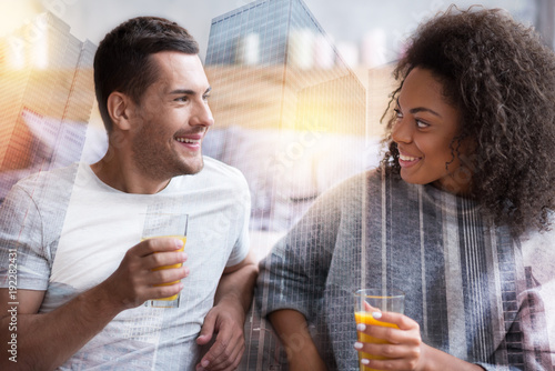 Keuken foto achterwand Sap Healthy lifestyle. Joyful positive delighted couple holding glasses and looking at each other while drinking orange juice