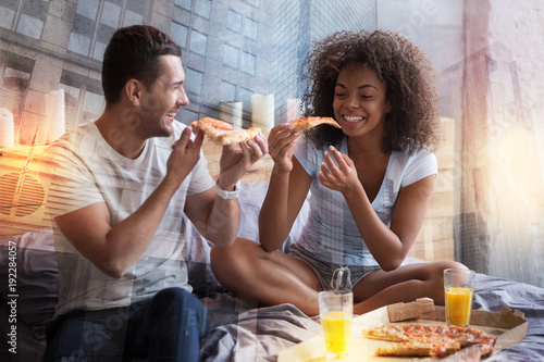 Playful mood. Positive nice sweet couple sitting together and eating pizza while having fun with each other