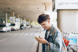 Young asian passenger waiting for taxi at the airport with phone - 192285484