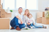 A happy family moves to a new apartment. Mother, father and child with boxes in the room of the new house. - 192286443