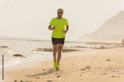 Fotobehang Hardlopen Jogging on a tropical sandy beach near sea / ocean.