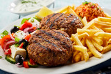 Traditional bifteki with Greek salad and chips - 192290041
