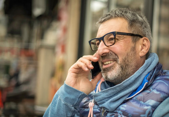 Middle-aged man with a gray beard and glasses talking on a mobile and smile