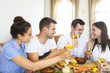 Friends with white wine toasting over served table with food