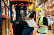 Quadro Warehouse workers working together with forklift loader