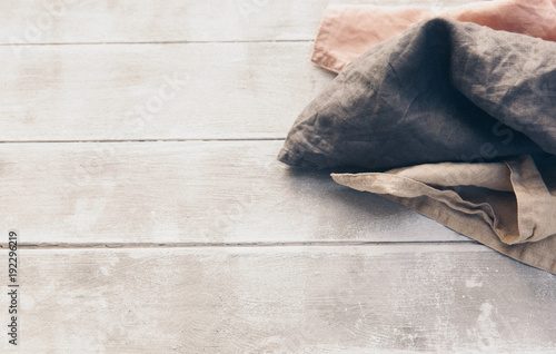Linen cloth napkins in brown and beige natural colors folded and tied with string isolated on wooden background