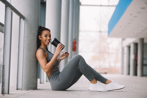 Young sporty girl leaning on the pillar and resting after workout.
