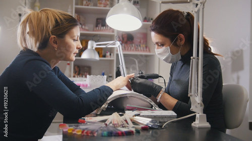 Poster Manicure Small business - manicurist - nail master in medical mask doing professional manicure