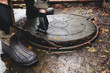 Hands opens sewer hatch by mounting