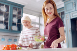 Healthy dish. Charming young woman and her elderly mother making a salad together, the younger woman holding a bowl with vegetables while the older one cutting - 192307087