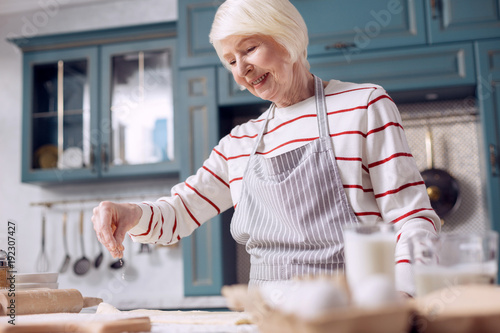 Pastry chef. Pleasant upbeat senior woman in an apron making dough in the kitchen and sprinkling it with some flour