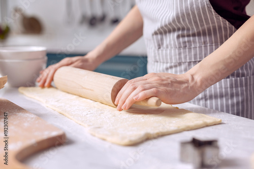 Cooking skills. The focus being on the delicate hands of a young woman wearing an apron and using a rolling spin to roll out dough on the kitchen counter