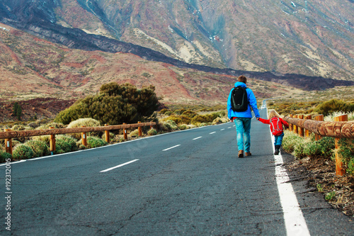 father with little daughter walking on road, family travel