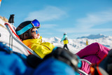 Picture of smiling sportswoman lying on winter deckchair