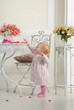 Little girl in dress near table for tea, in interior