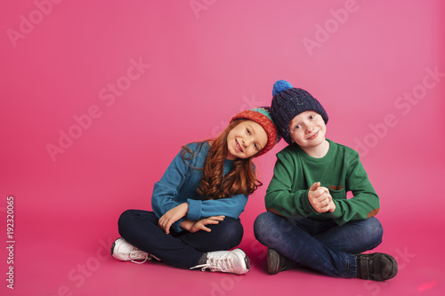 Leinwandbild Motiv Cheerful girl and her brother sitting on floor and smiling to camera