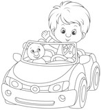 Little boy with his teddy bear in a toy car