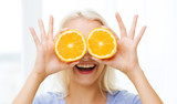 happy woman having fun covering eyes with orange - 192330257
