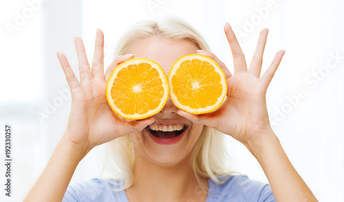 happy woman having fun covering eyes with orange - 192330257