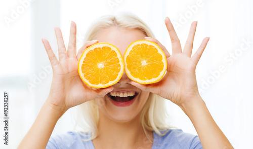 happy woman having fun covering eyes with orange
